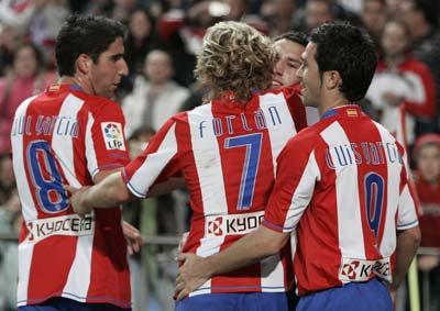 Los jugadores del Atlético se abrazan celebrando un gol.
