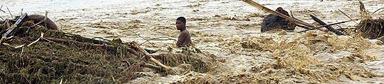 Un hombre arrastrado por la crecida del río Haina, a su paso por el municipio de Villa Altagracia (República Dominicana).