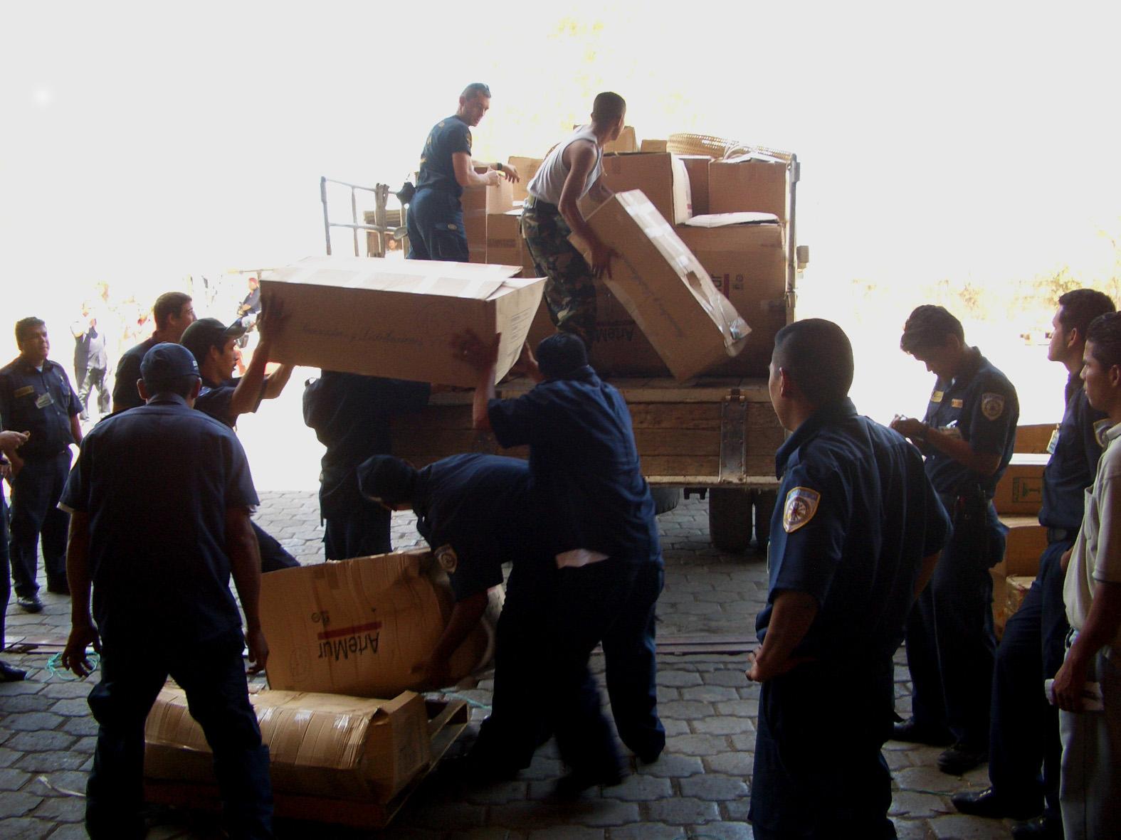 Los  bomberos cargan material en un camión