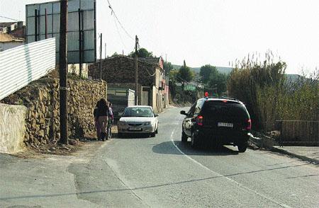 Peatones intentan caminar por la calzada de la carretera que divide la pedanía esquivando los coches.