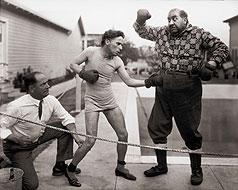 Boxeando con el actor Mack Swain con su vestuario de La quimera del oro (The Gold Rush). El árbitro es el boxeador real Kid McCoy (1923-1925)