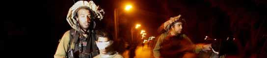Soldados israelíes llevan detenidos a varios jóvenes palestinos en la entrada de Israel. (REUTERS)