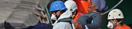 Miembros de Cruz Roja ayudan a desembarcar a unA mujer que llegó con este grupo de inmigrantes. MANUEL LÉRIDA / EFE