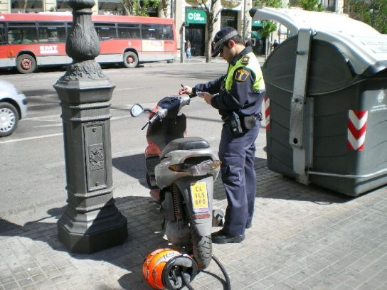 Un policía multa una moto en Marqués de Sotelo