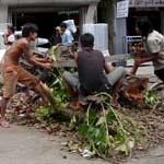 Un grupo de birmanos corta un árbol en la calle. (EFE)