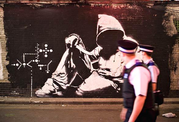 Túnel del grafito (24/6/2008). Una galería para el grafiti. Dos policías pasan ante uno de los grafitis de Banksy pintado en el túnel abandonado cercano a la estación de Waterloo en Londres. El espacio ha sido reutilizado por Banksy y otros artistas como espacio expositivo. FOTOGALERÍA: El túnel del grafiti en Londres