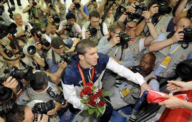 Michael Phelps. Asediado por los focos El nadador estadounidense Michael Phelps (c) se abre paso en medio de una multitud de fotógrafos después de ganar la competición de relevos. (EFE)
