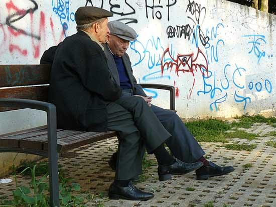 Dos ancianos conversan en un banco