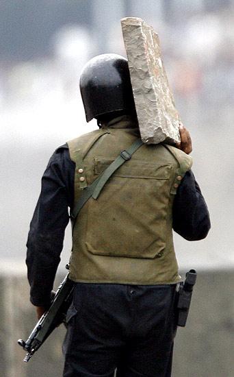 Comando indio con una piedra (28/11/2008). Escudo. Un soldado indio se protege con una losa durante un tiroteo frente al hotel Taj de Bombay.