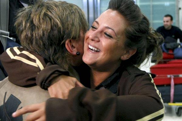 Dos mujeres se abrazan tras la llegada de una de ellas desde Tailandia