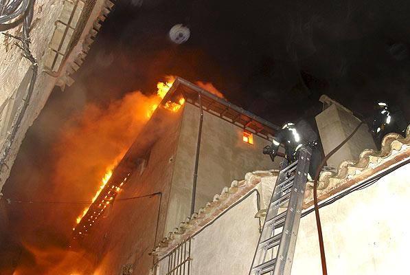 Incendio en CHinchón (5/12/2008). Incendio en Chinchón. Dos bomberos trabajan en la extinción de un incendio en la cubierta de un edificio del siglo XVI en el casco histórico de la localidad madrileña de Chinchón.