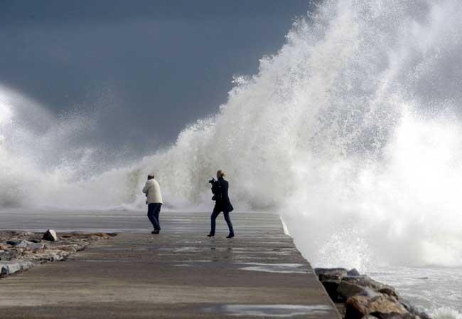 Una pareja en la playa del Bogatell de Barcelona, azotada hoy por el fuerte temporal de viento y lluvia.