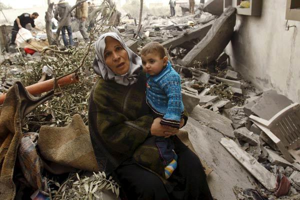 Una mujer palestina, con un niño, sentados sobre las ruinas de su casa