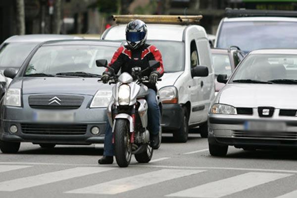 Una moto, entre dos coches.