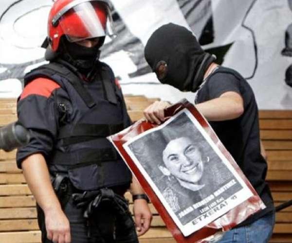 Dos agentes de la Ertzaintza retiran la foto de una presa de ETA.
