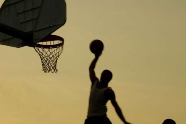 Un joven juega al basket.