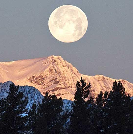 La Luna sobre una montaña nevada.