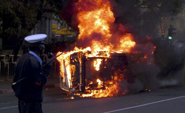 Coche en llamas en Nairobi. Un policía camina cerca de un automóvil en llamas a lo largo de la avenida Kenyatta, en la capital de Kenia, Nairobi. La causa del incendio no ha sido determinada.