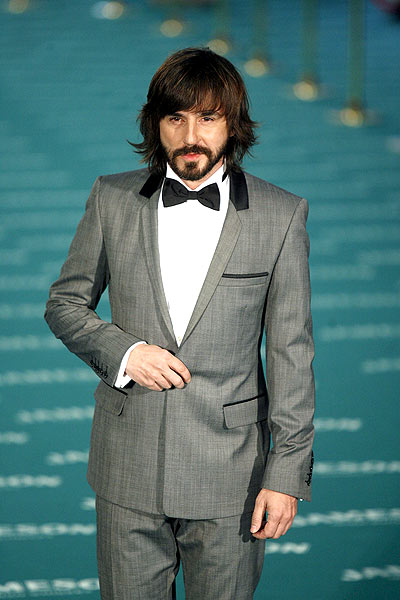 La gala de los Goya (Millán). Santi Millán, elegantísimo con un smoking gris claro, solapa estrecha y pajarita amplia.