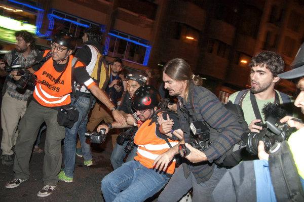 <p>Un fotógrafo es transladado por sus compañeros tras recibir un pelotazo de goma en el tobillo durante las cargas de los antidisturbios en el madrileño Paseo del Prado el 25-S.</p>