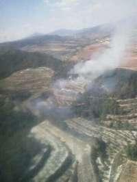 Sucesos.- Efectivos aéreos y terrestres trabajan en la extinción de un incendio forestal en Moixent