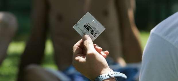 Un joven sostiene un preservativo