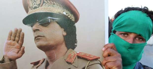 Un seguidor de Gadafi con un cartel del dictador libio
