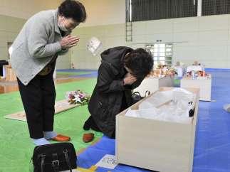 Dos mujeres velan un cadáver del terremoto de Japón