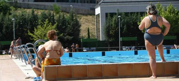 Bañistas tomando el sol en la piscina del barrio del Pilar.