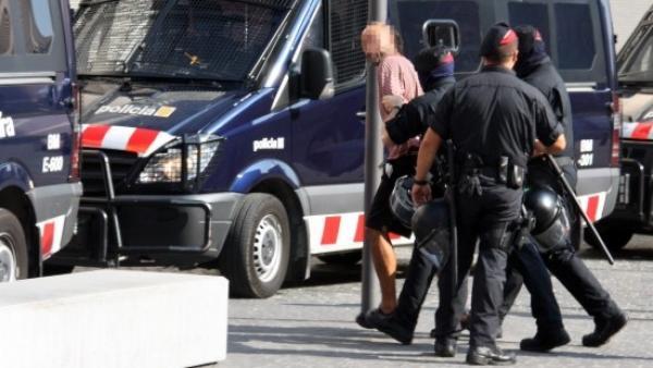 Los Mossos antidisturbios detienen a un joven imputado.