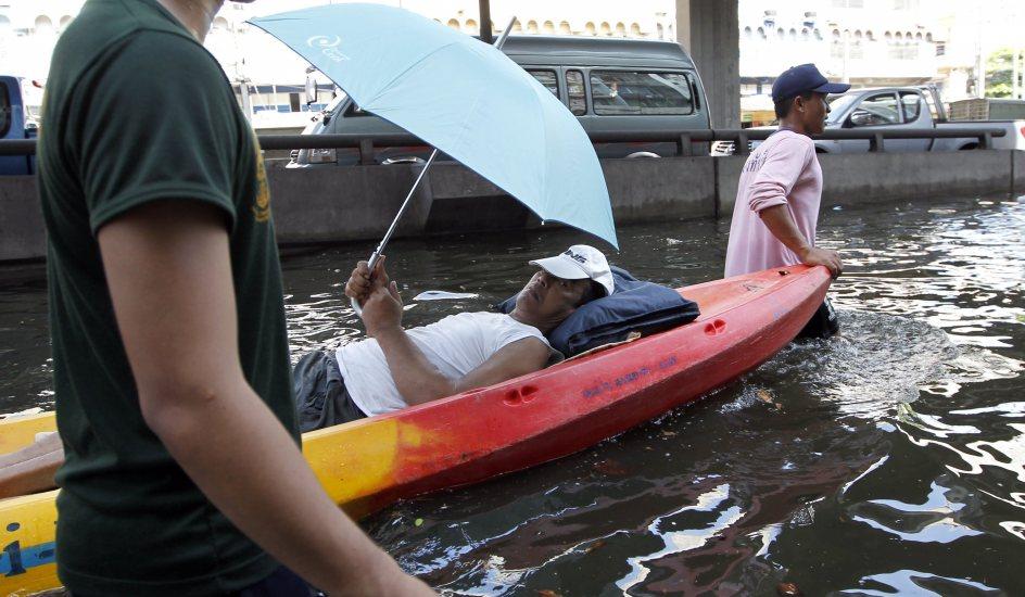 Bajo las aguas. Un hombre enfermo es evacuado en barca por una calle inundada de un barrio residencial en Bangkok (Tailandia). Muchos miles de residentes abandonan las áreas de la metrópoli en las que empeoran las inundaciones.
