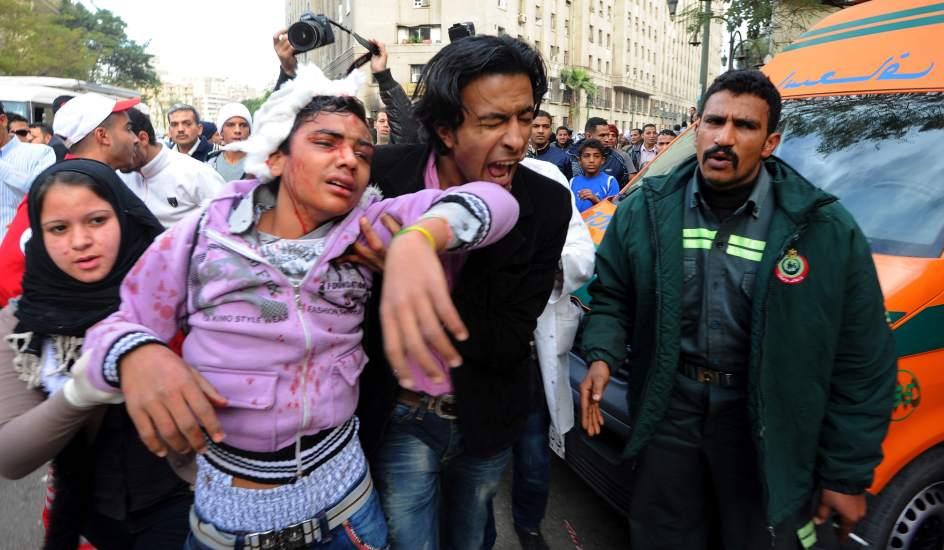 Disturbios en El Cairo. Un opositor recibe la ayuda de sus compañeros tras resultar herido durante los enfrentamientos con las fuerzas de seguridad egipcias.