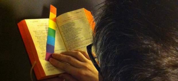 Un religioso lee una Biblia, con un marca-páginas multicolor