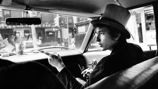 'Bob Dylan with top hat pointing in car'