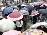 Varias personas se refugian de la lluvia bajo el paraguas