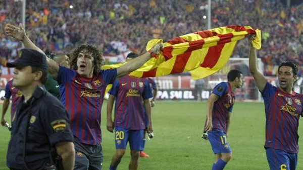 Xavi y Puyol, con la bandera