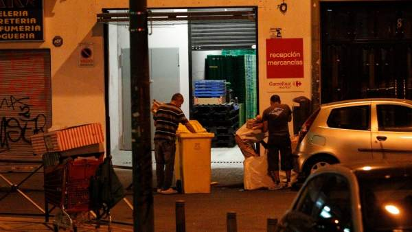 Un grupo de personas busca comida en contenedores