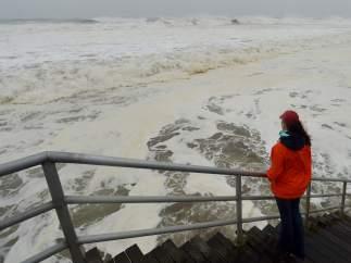 Una mujer mira los efectos de Sandy en Rockaway Beach