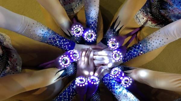 Las manos de las gimnastas y las luces de las mazas.