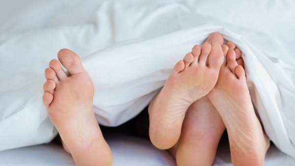 Pareja bajo las sábanas