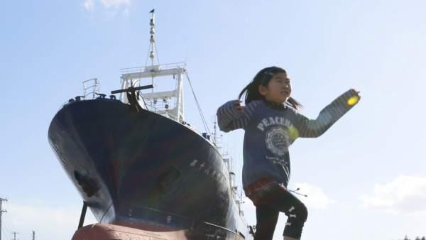 Una niña juega junto a un barco pesquero arrastrado mar adentro por el tsunami de 2010 en el norte de Japón.