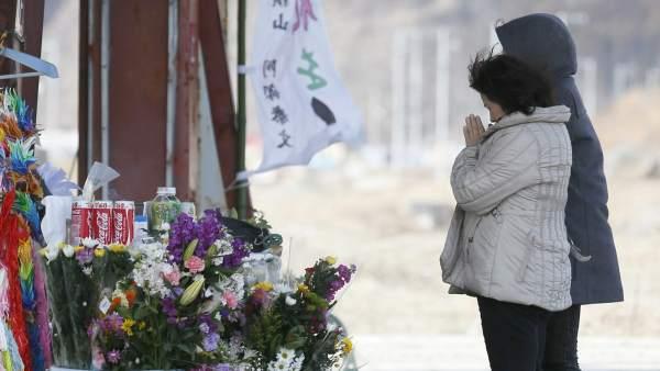 Residentes rezan en una de las ciudades japonesas devastadas por el tsunami de 2010.