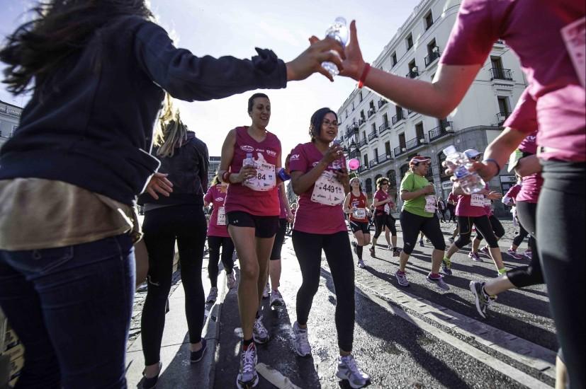 Agua para combatir el calor. Dos atletas beben agua para hidratarse durante la carrera.