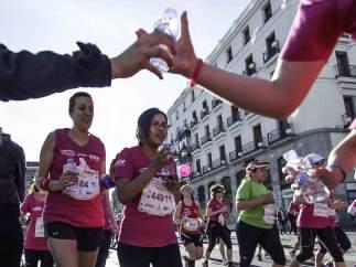 Un voluntario le da una botella de agua a una corredora