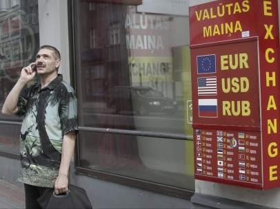 Un hombre permanece junto a una oficina de cambio de moneda en Riga (Letonia).