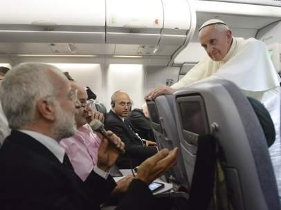 El papa Francisco (dcha) escucha la pregunta de uno de los periodistas durante una rueda de prensa dada a bordo del avión que le traslada a Italia tras abandonar Río de Janeiro (Brasil).
