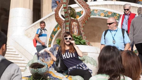 Una turista es fa una foto al popular Drac de Gaudí del Park Güell.