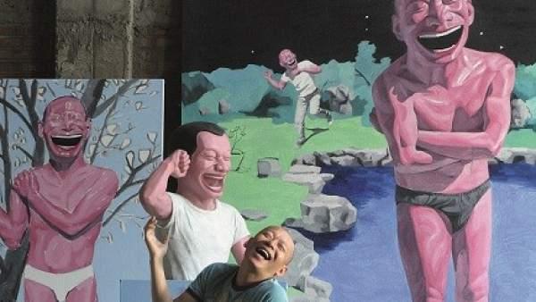 Yue Minjun, el pintor chino de la risa, posa junto a sus obras.