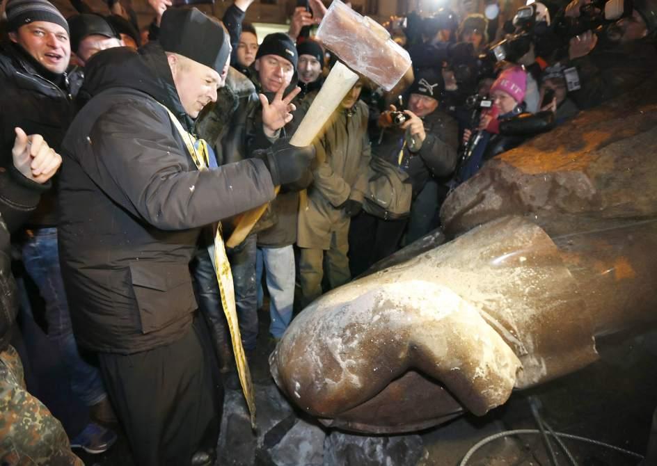 La hoz... y el martillo. Un activista proeuropeo destroza a golpes de mazo la estatua derribada de Lenin en el centro de Kiev, Ucrania.