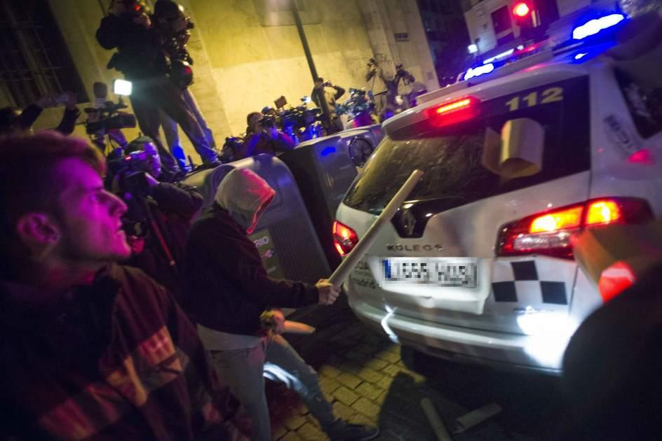 Disturbios en el centro de Madrid. Un manifestante golpea la luna trasera de un coche de Policía Nacional con un tubo en la calle San Sebastián de Madrid.
